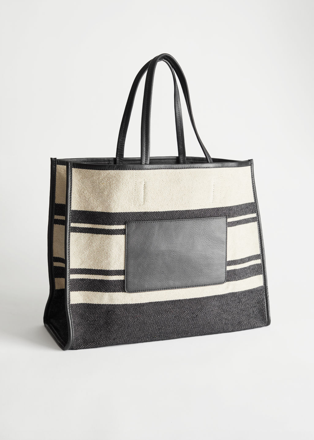 StillLife Front Image of Stories Canvas Tote Bag in Black