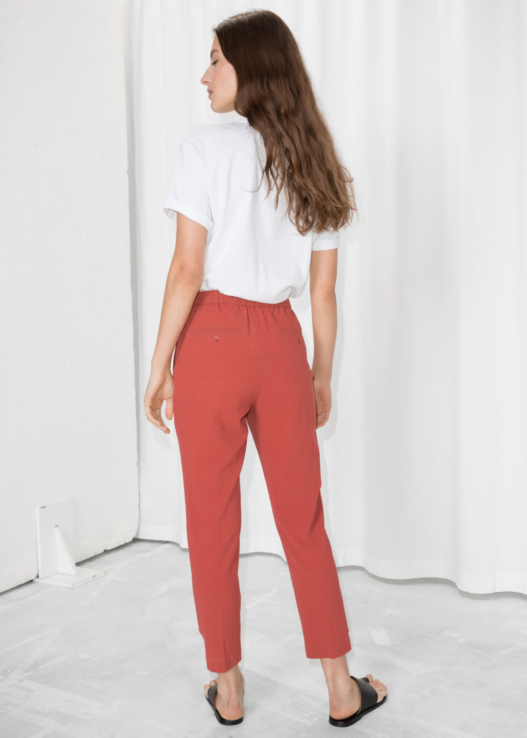 Model back image of Stories tapered cotton trousers in red