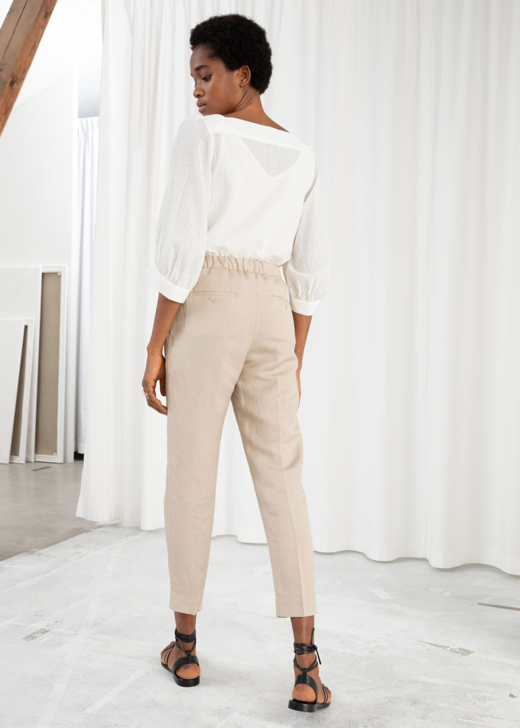 Model back image of Stories tapered cotton trousers in beige