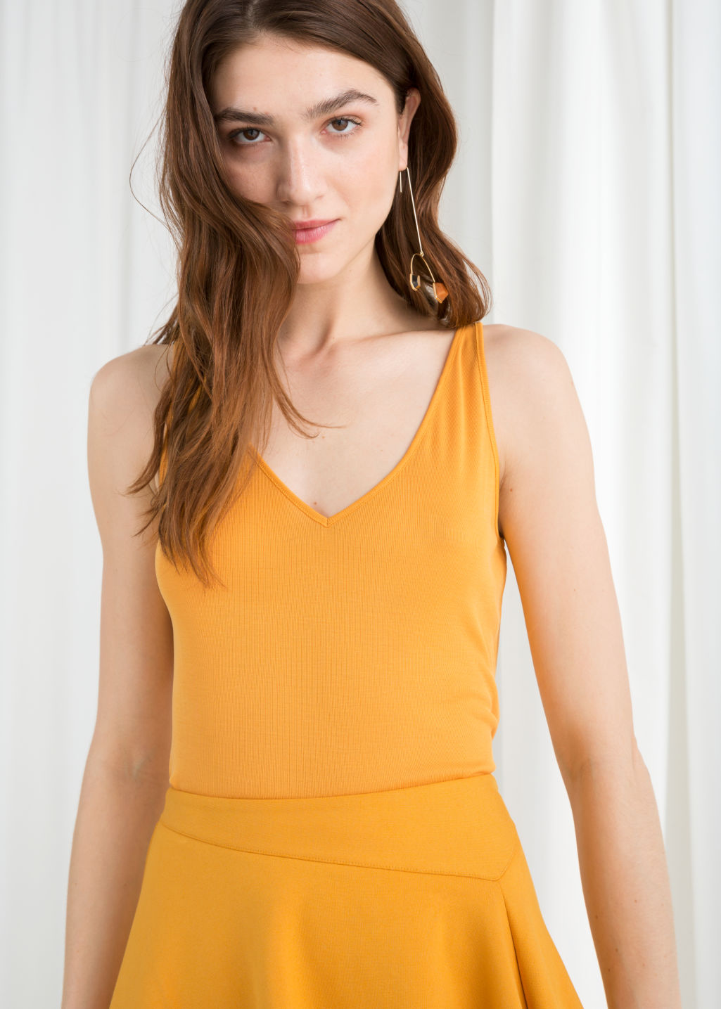 Model front image of Stories ribbed v-neck top in yellow