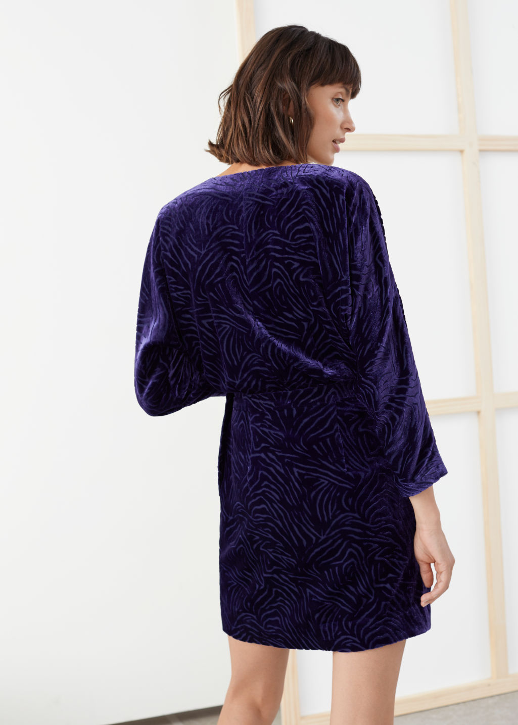 Model back image of Stories velvet wrap dress in purple