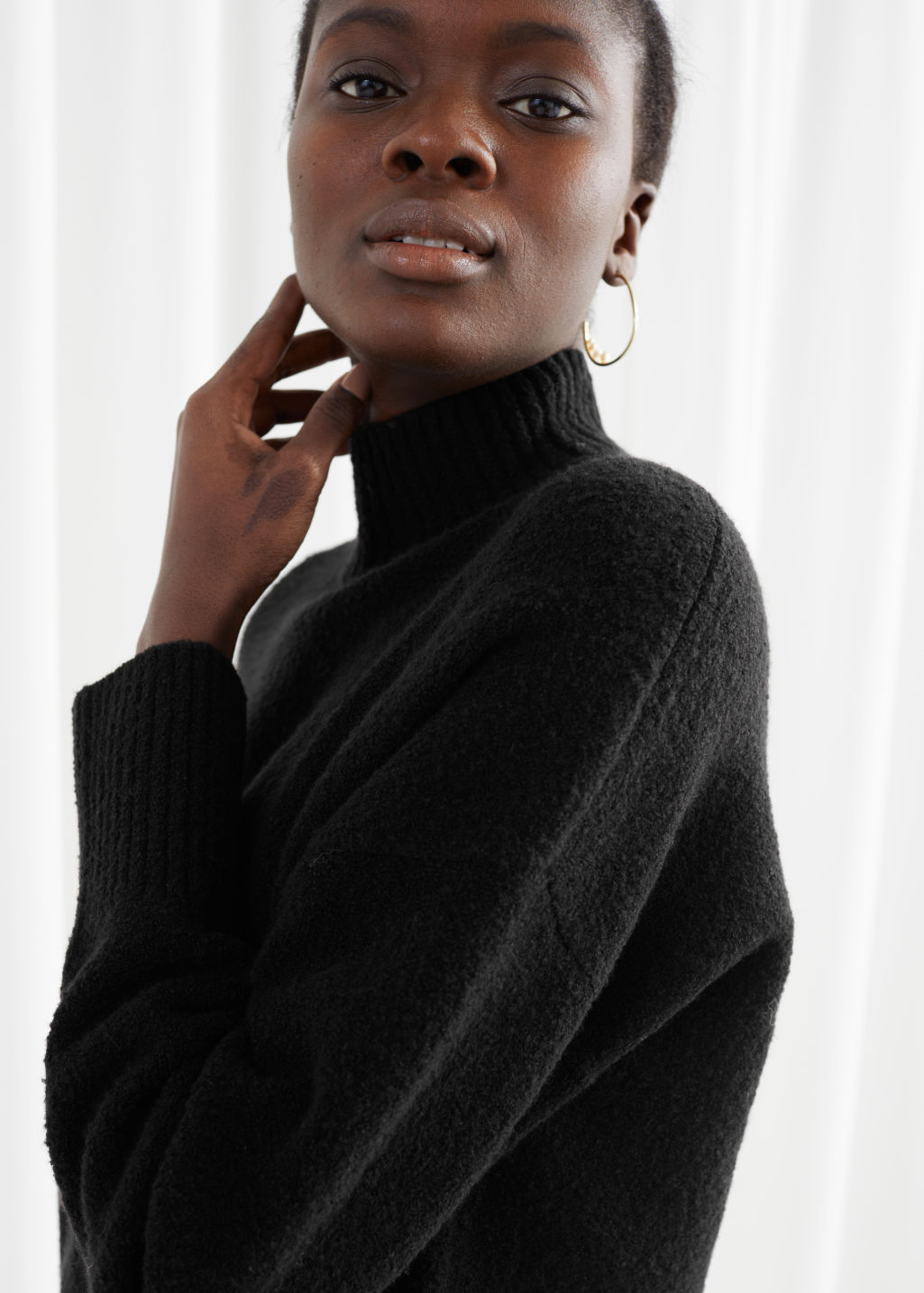 Model side image of Stories cropped mock neck sweater in black