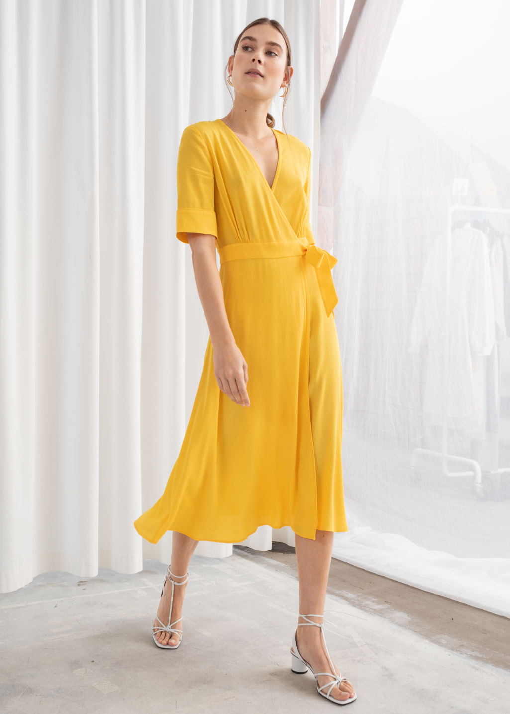 Model front image of Stories midi wrap dress in yellow