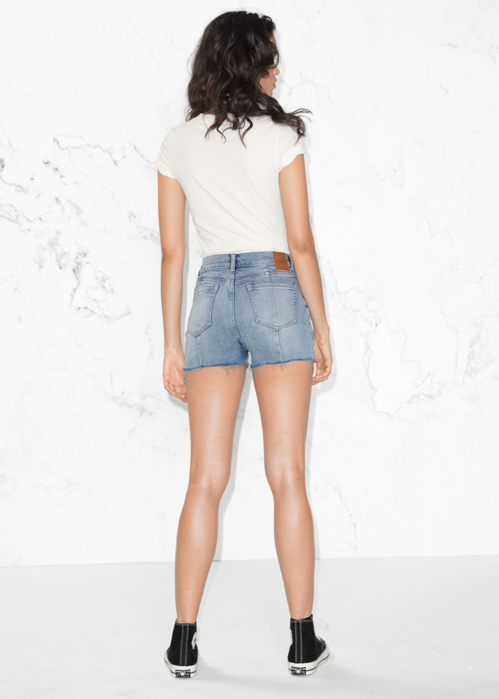 Model back image of Stories raw hem denim shorts  in blue