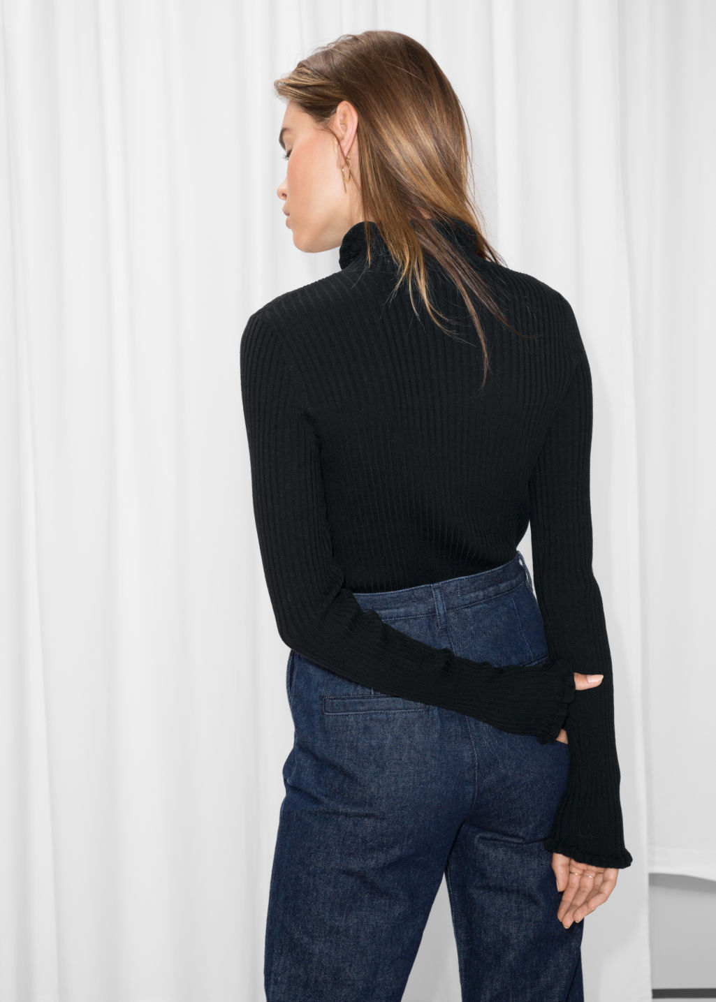 Model back image of Stories ruffles and ribbed turtleneck in black