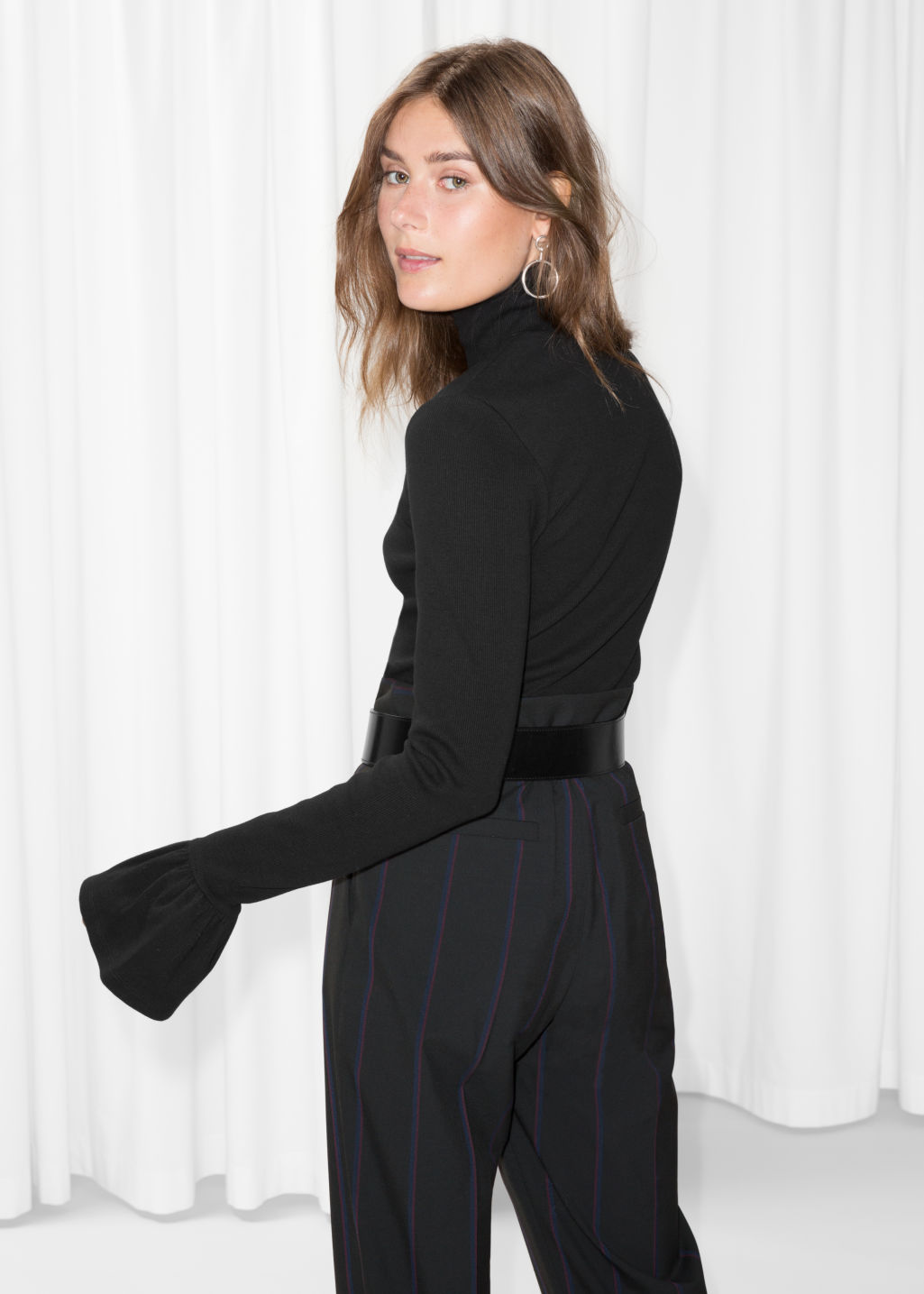 Model back image of Stories trumpet sleeve turtleneck top in black