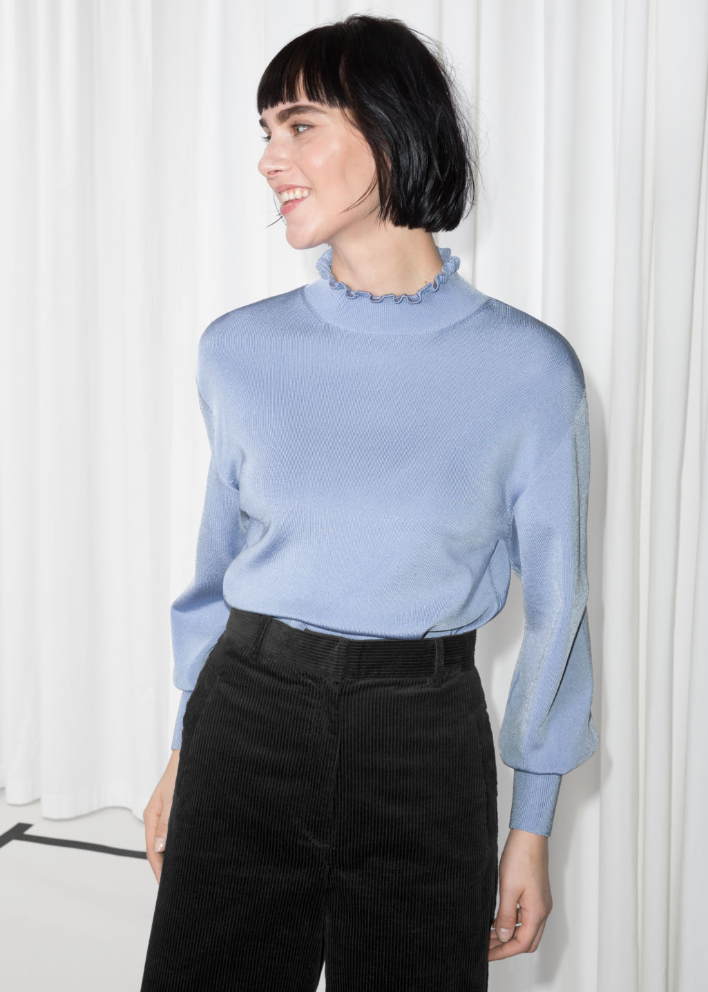 Model front image of Stories frill mock neck top in blue