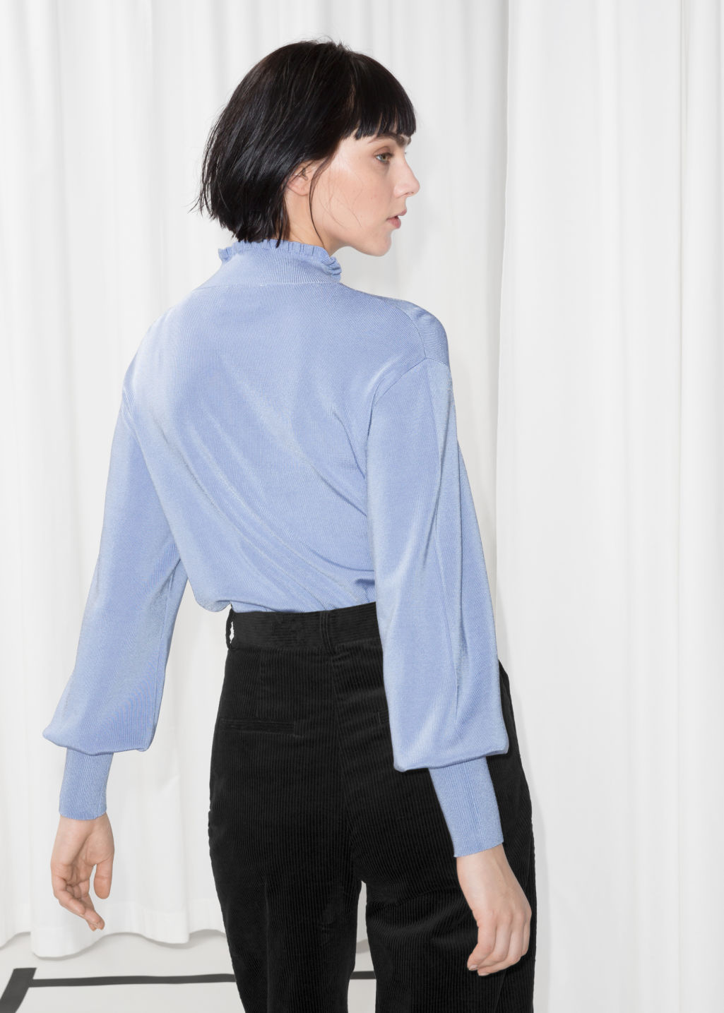 Model back image of Stories frill mock neck top in blue
