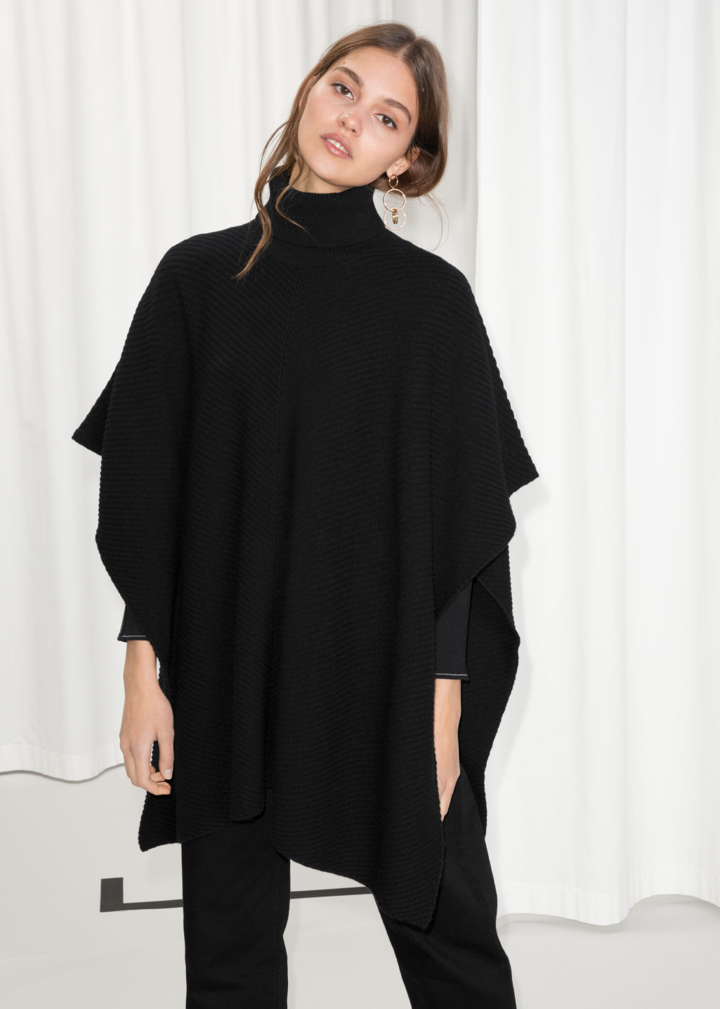 Model front image of Stories turtleneck cape in black