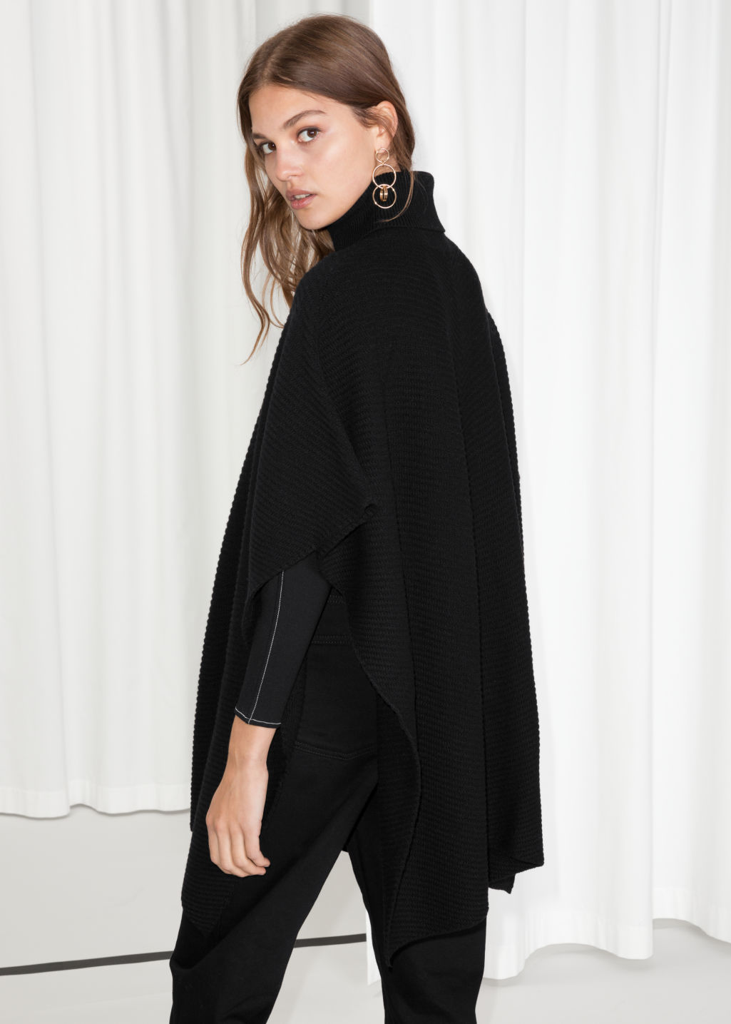 Model back image of Stories turtleneck cape in black