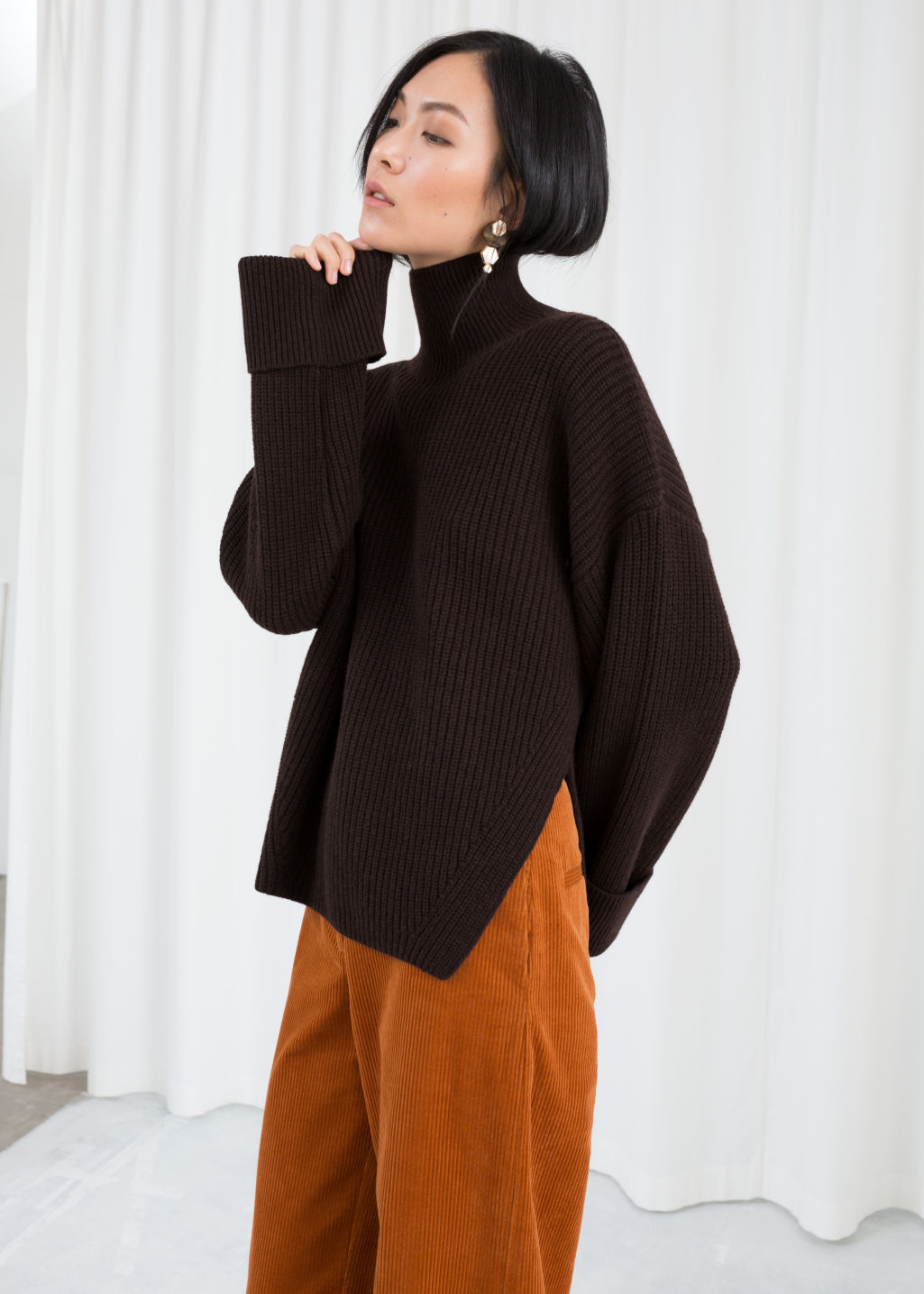 Model front image of Stories oversized side-slit turtleneck in brown