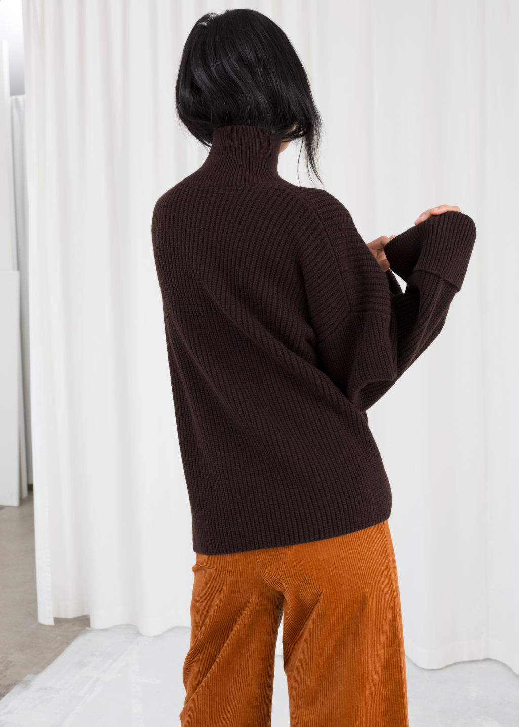 Model back image of Stories oversized side-slit turtleneck in brown