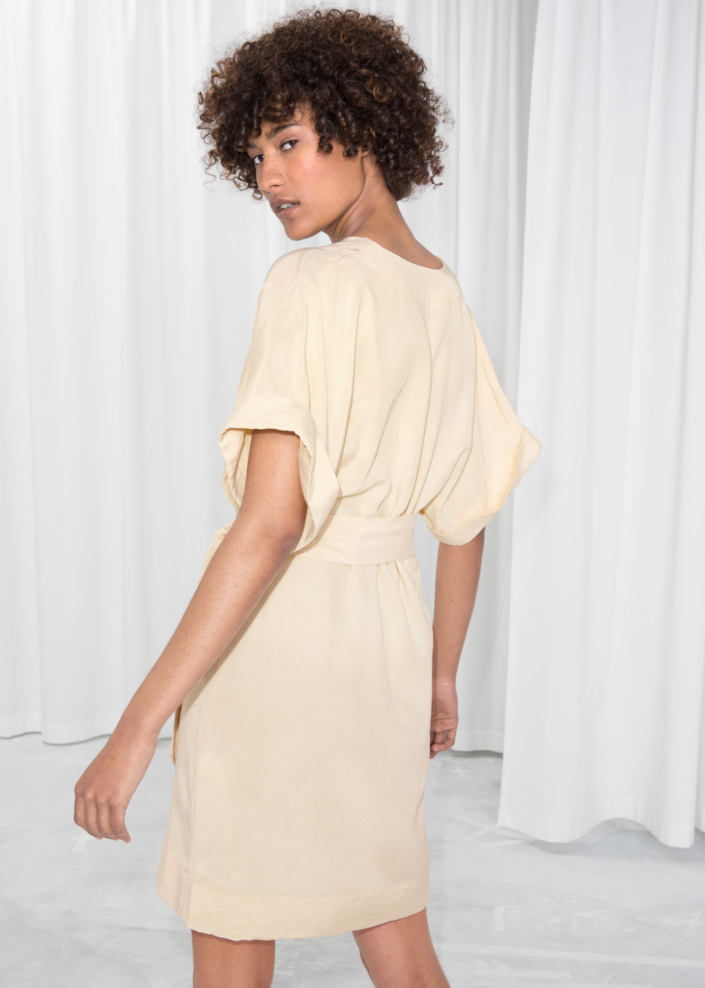 Model back image of Stories belted wrap mini dress in beige