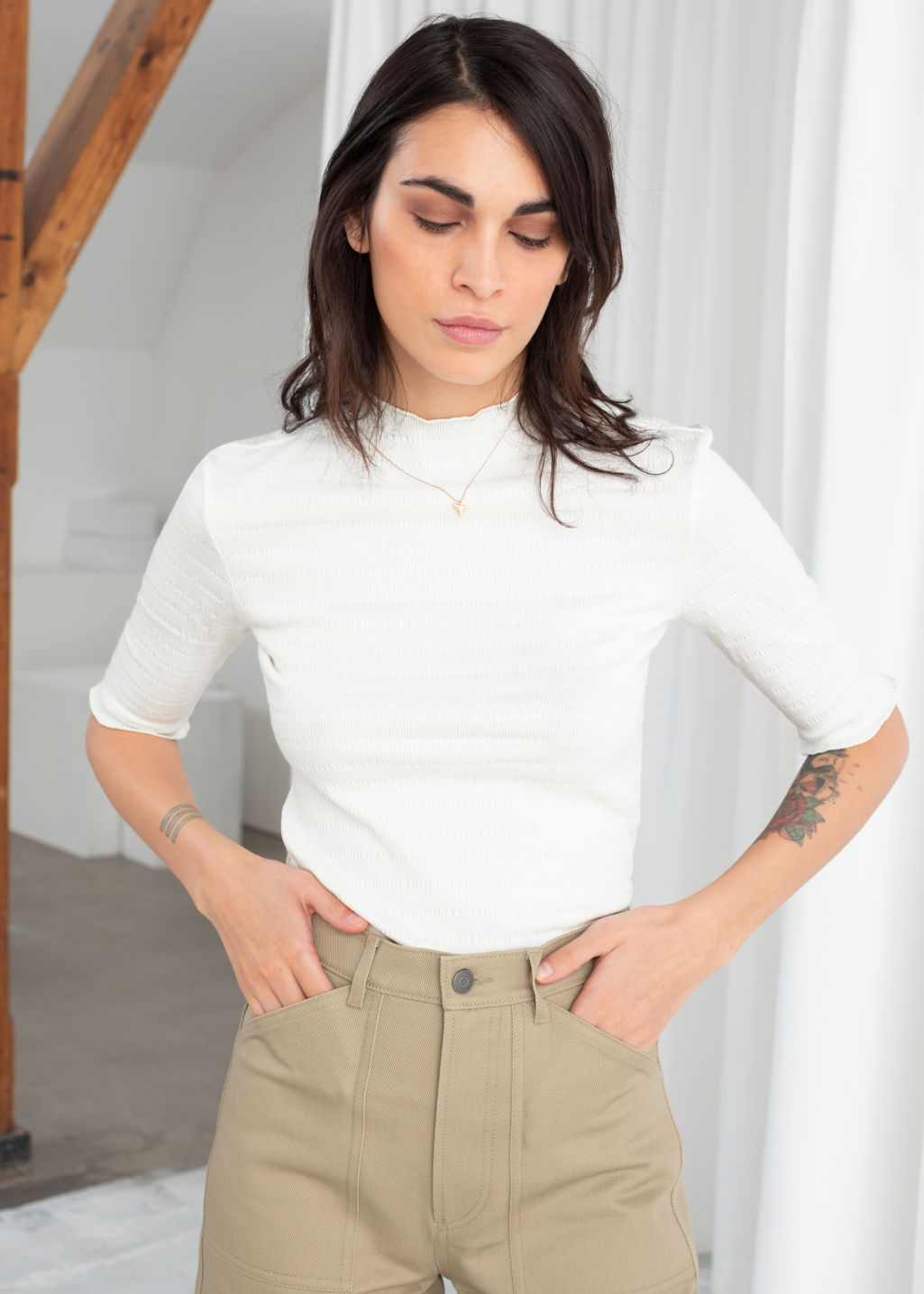 Model front image of Stories ruffle mock neck top in white