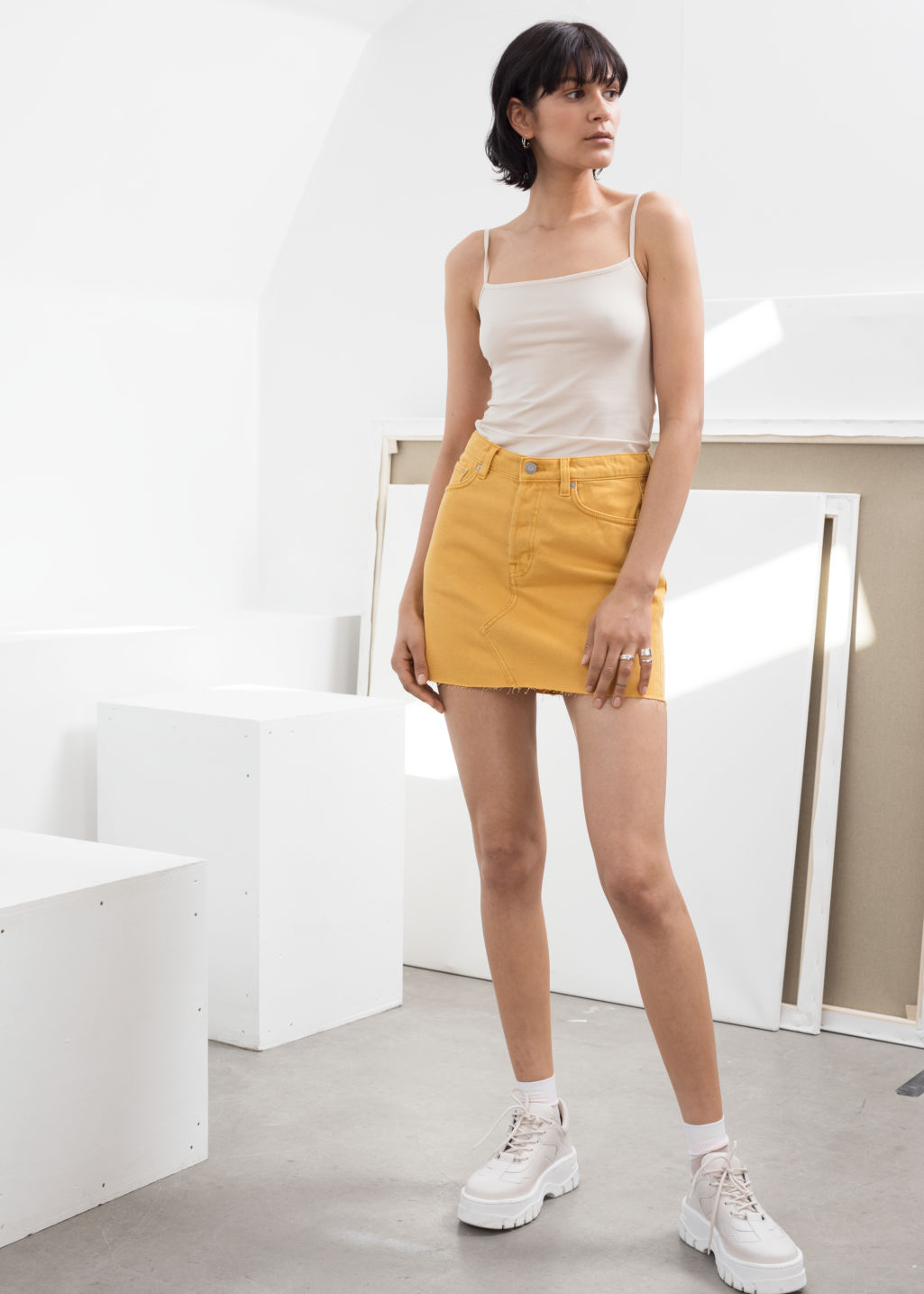 Model front image of Stories raw edge denim mini skirt in yellow