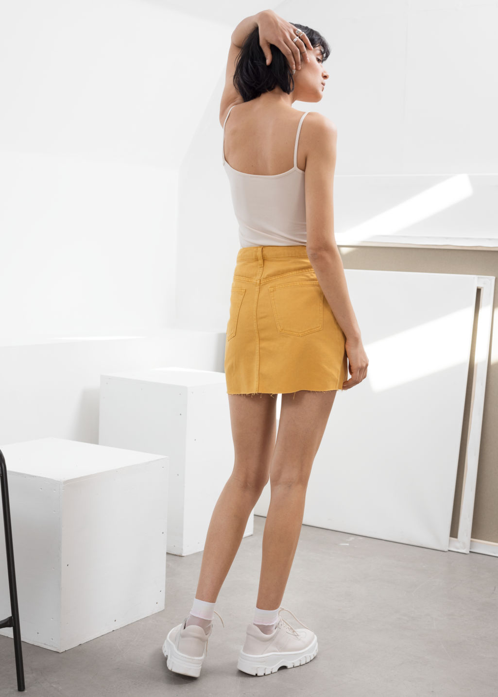 Model back image of Stories raw edge denim mini skirt in yellow