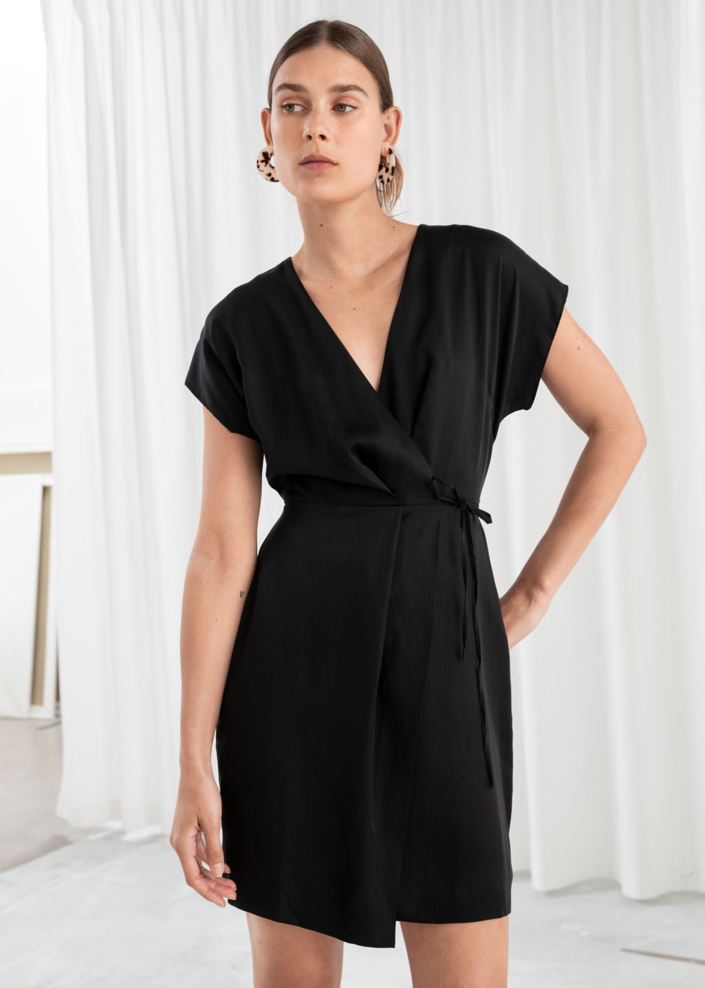 Model front image of Stories sleeveless wrap dress in black