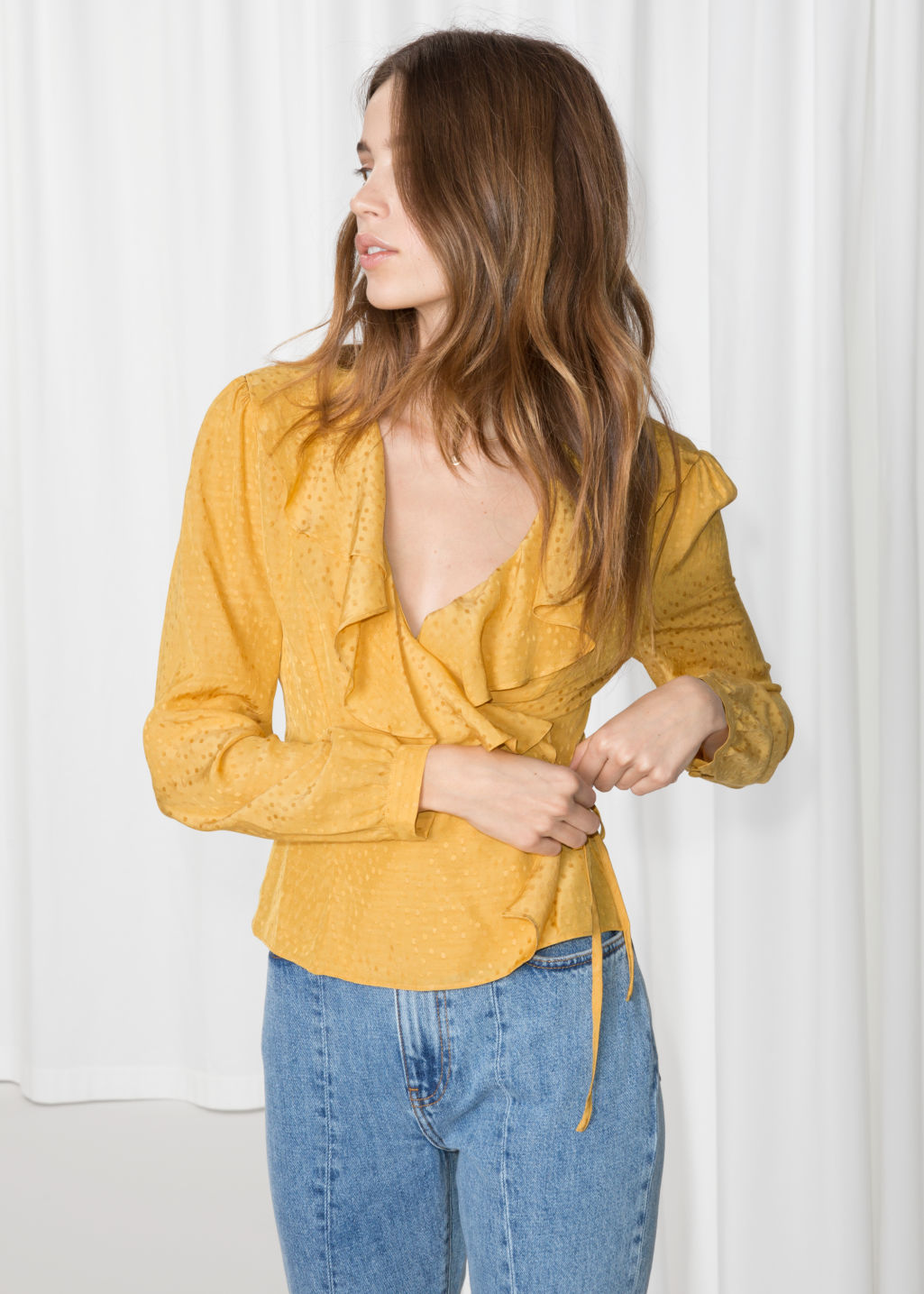 Model front image of Stories ruffle wrap blouse in yellow