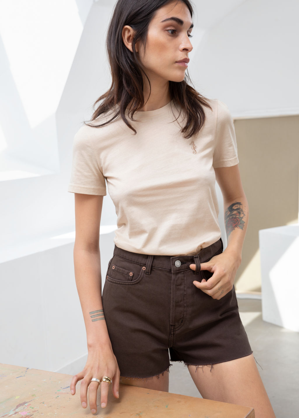 Model front image of Stories raw edge denim shorts in brown
