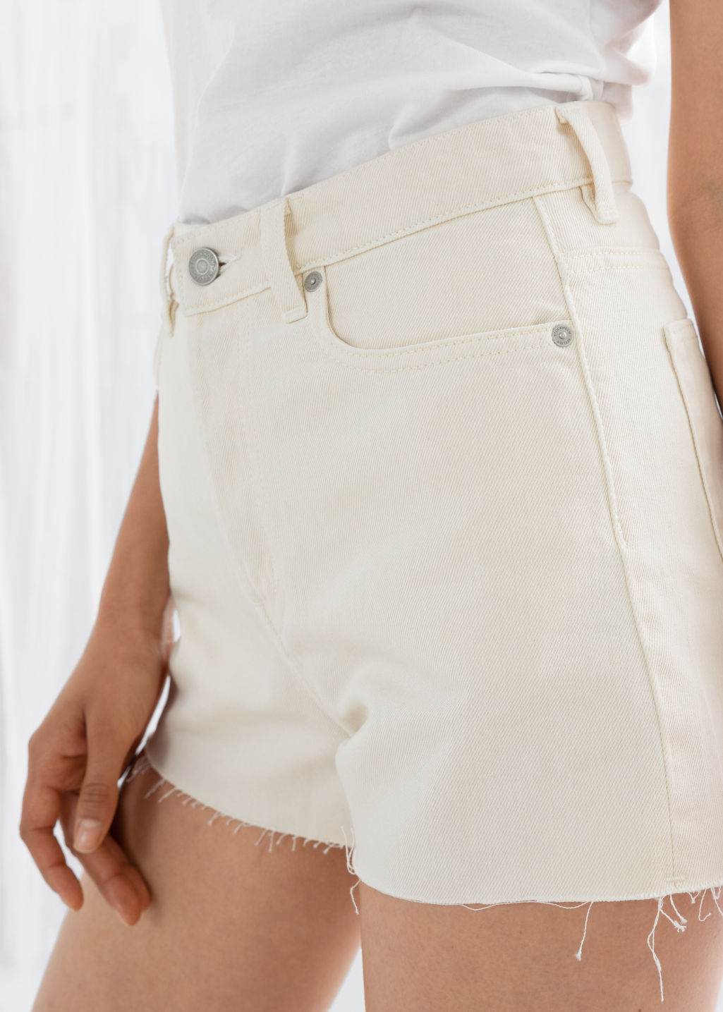Model back image of Stories raw edge denim shorts in white
