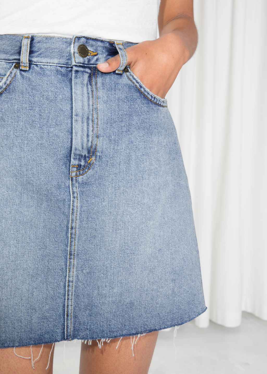 Model back image of Stories raw edge denim skirt  in blue