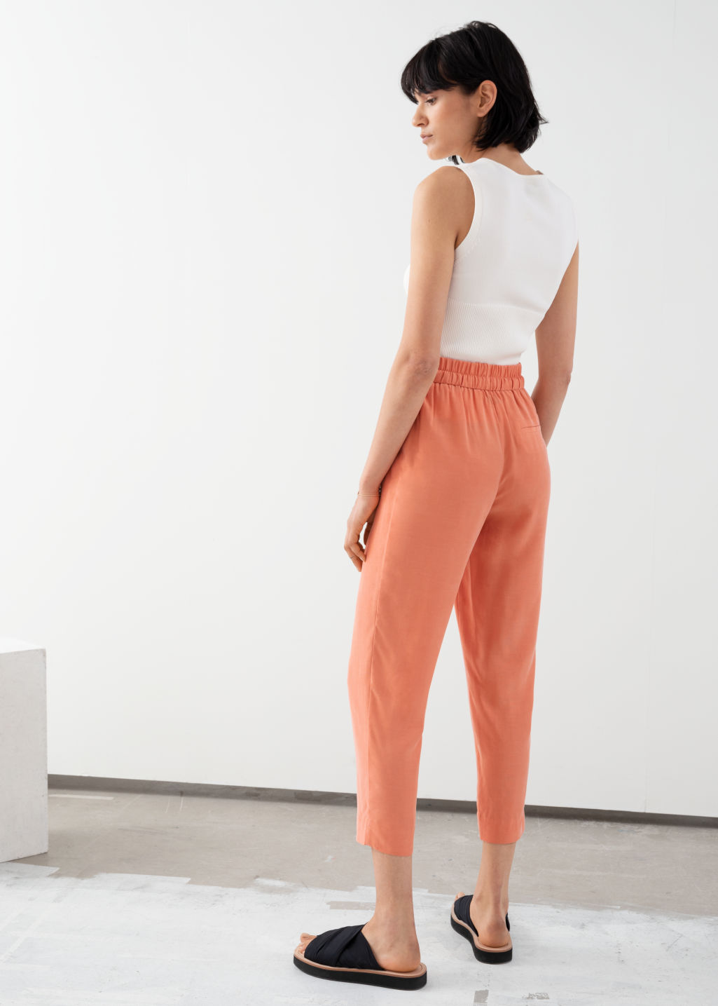 Model back image of Stories cupro blend jogger trousers in orange