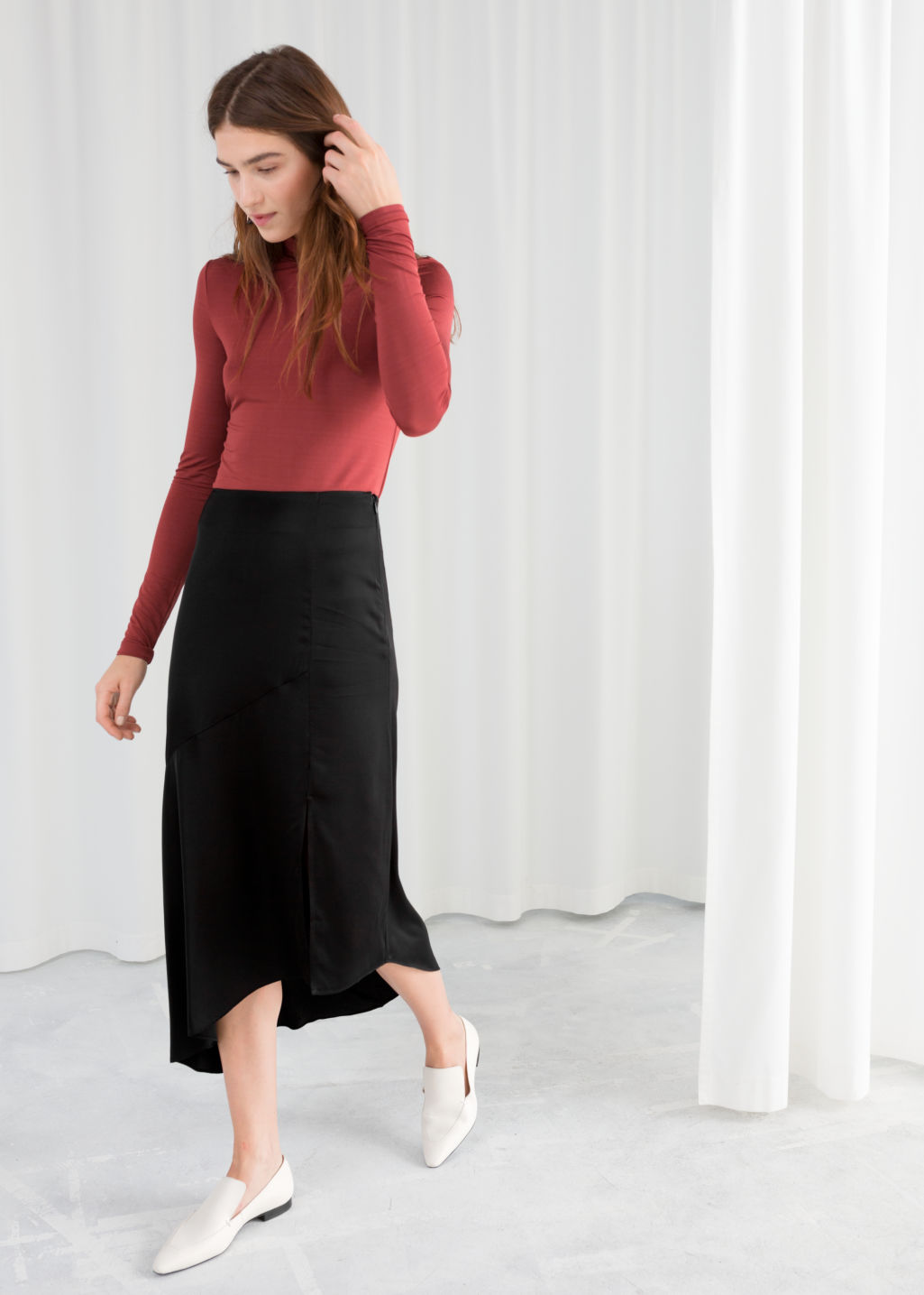 Model front image of Stories asymmetric slit midi skirt in black
