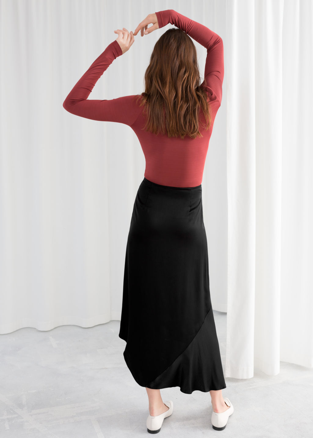Model back image of Stories asymmetric slit midi skirt in black
