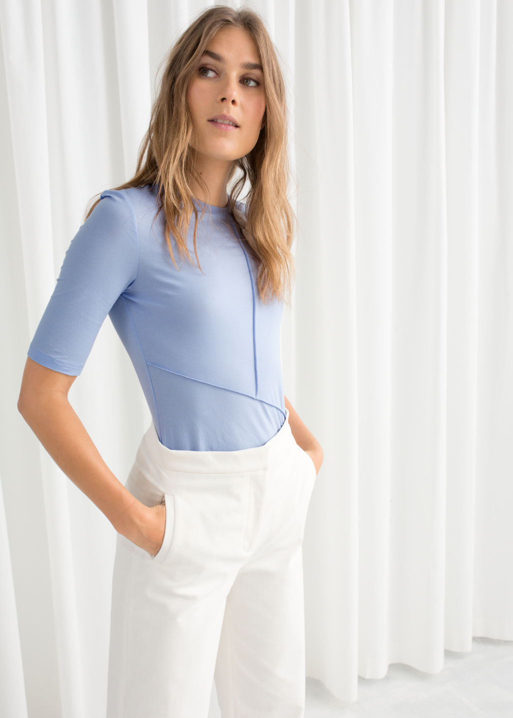 Model front image of Stories block seam mock neck top in blue