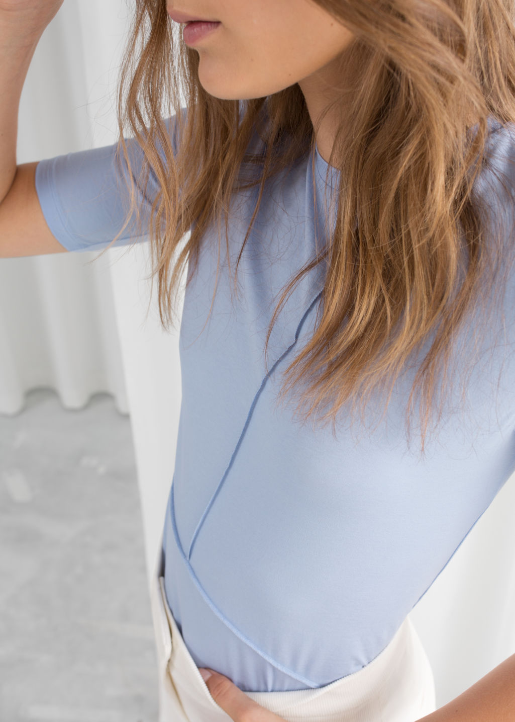 Model back image of Stories block seam mock neck top in blue