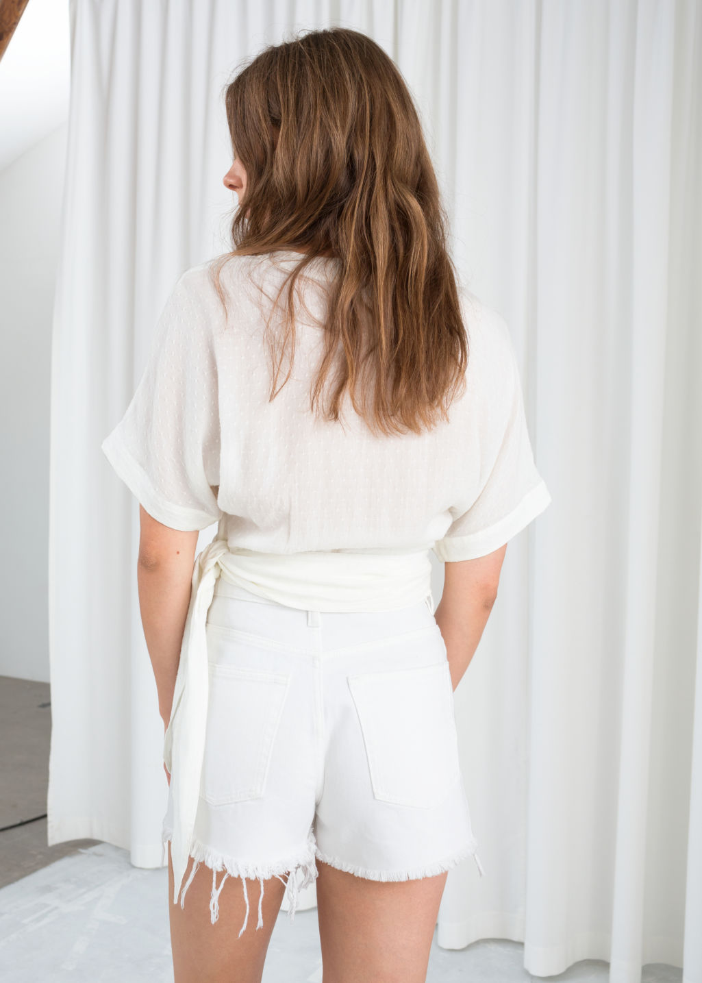 Model back image of Stories belted wrap blouse in white