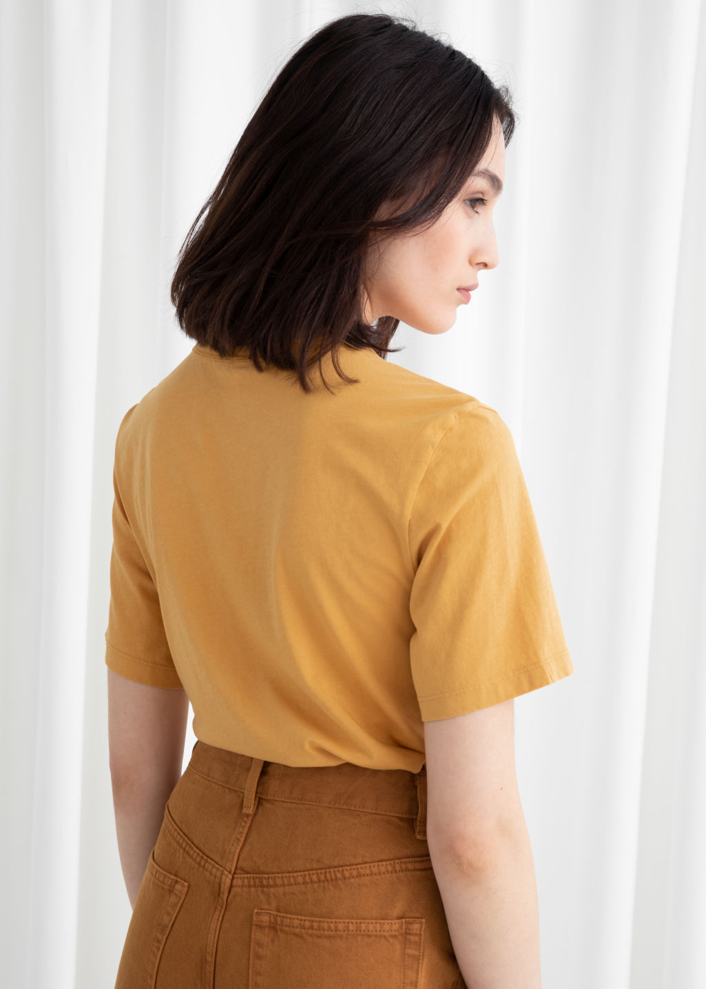 Model back image of Stories organic cotton tee in yellow