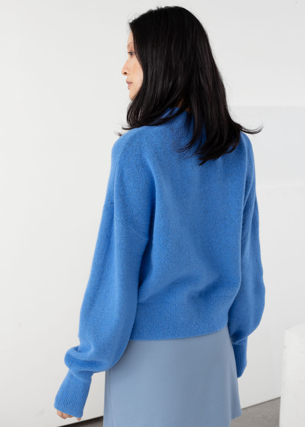 Model back image of Stories mock neck sweater in blue