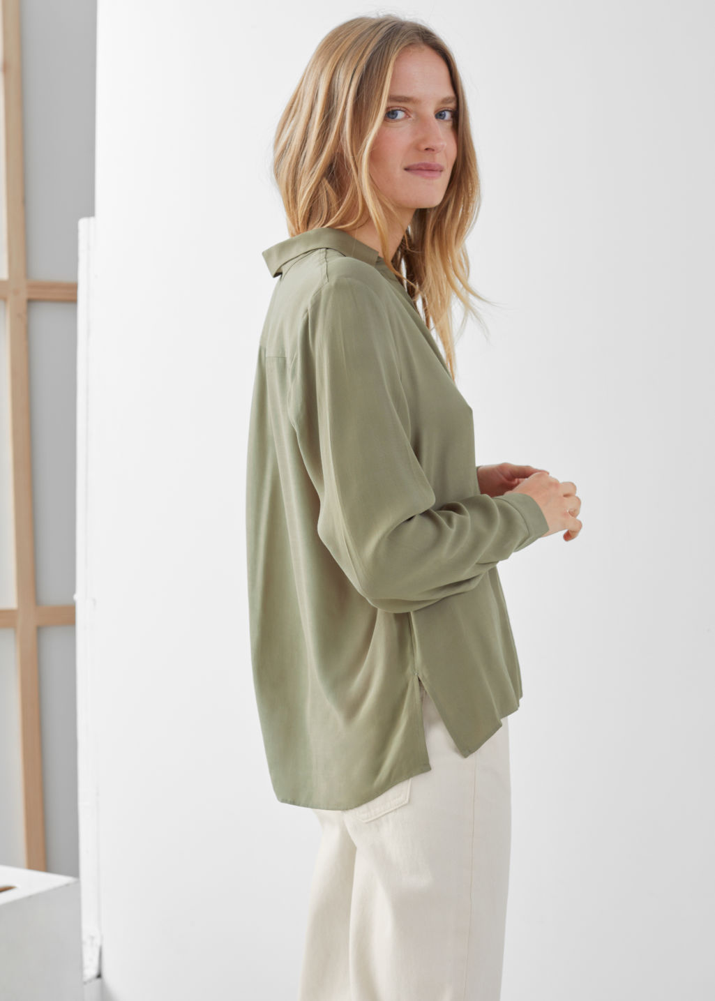 Model side image of Stories relaxed fit button up in green