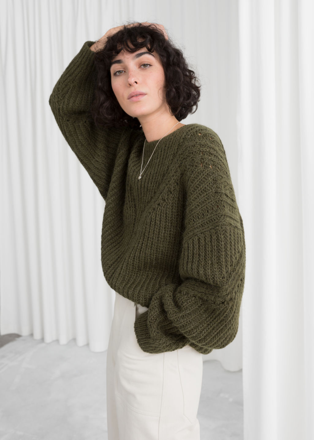 Model back image of Stories oversized curved knit sweater in green