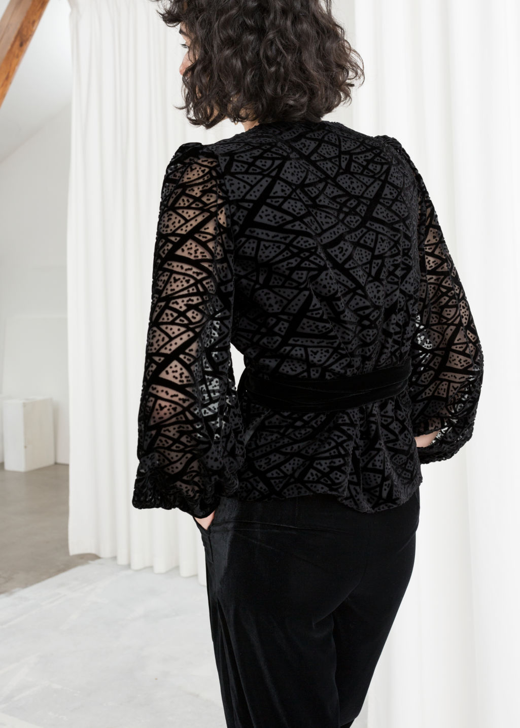 Model back image of Stories velvet mesh wrap top in black