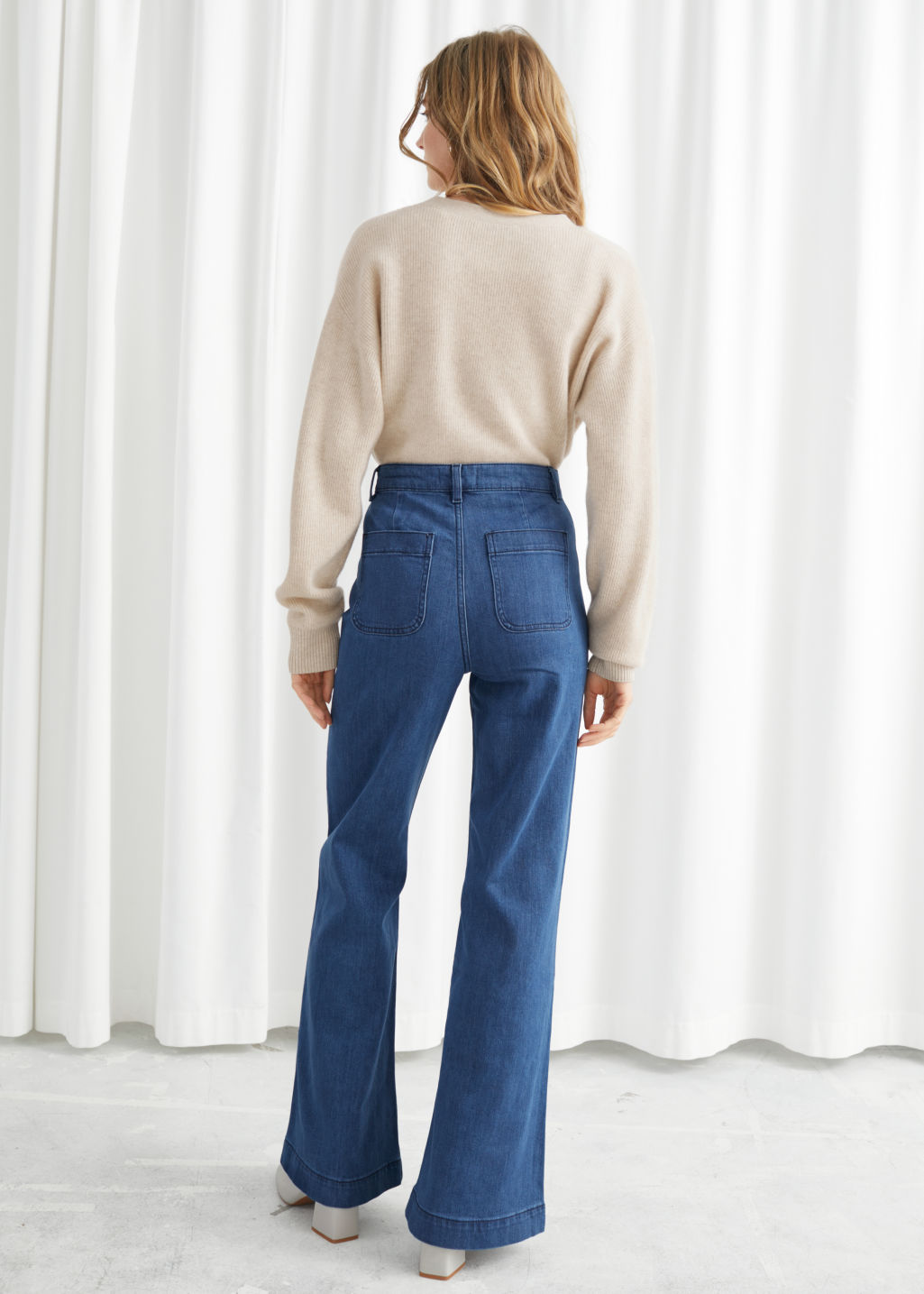 Model back image of Stories flared mid rise jeans in blue