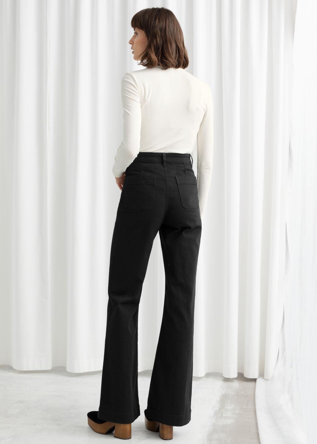 Model back image of Stories flared mid rise jeans in black