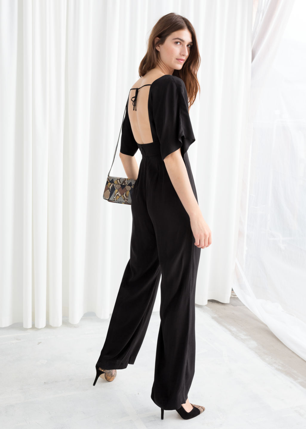 Model back image of Stories plunging v-cut jumpsuit in black