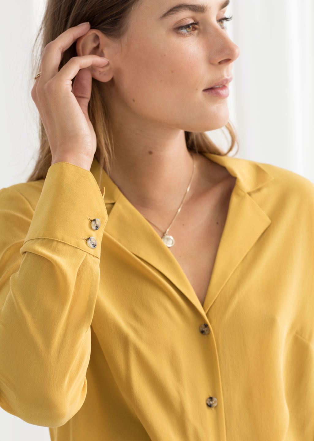 Model back image of Stories v-cut silk button up blouse in yellow