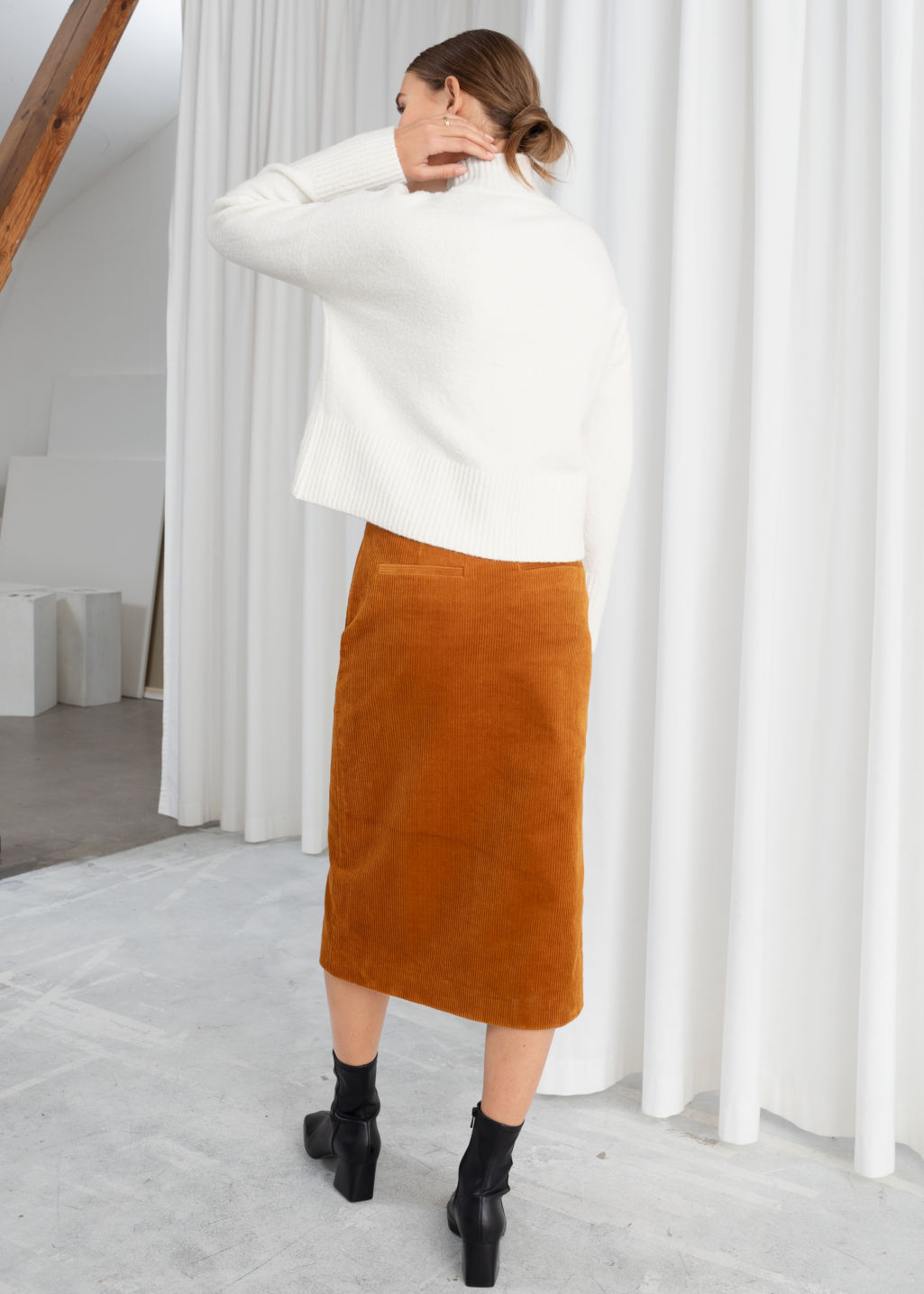 Model back image of Stories front slit corduroy midi skirt in orange