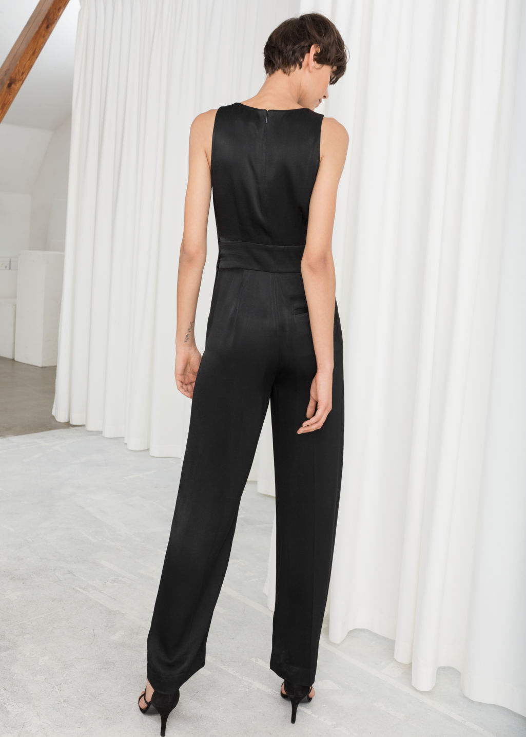 Model back image of Stories sleeveless satin jumpsuit in black