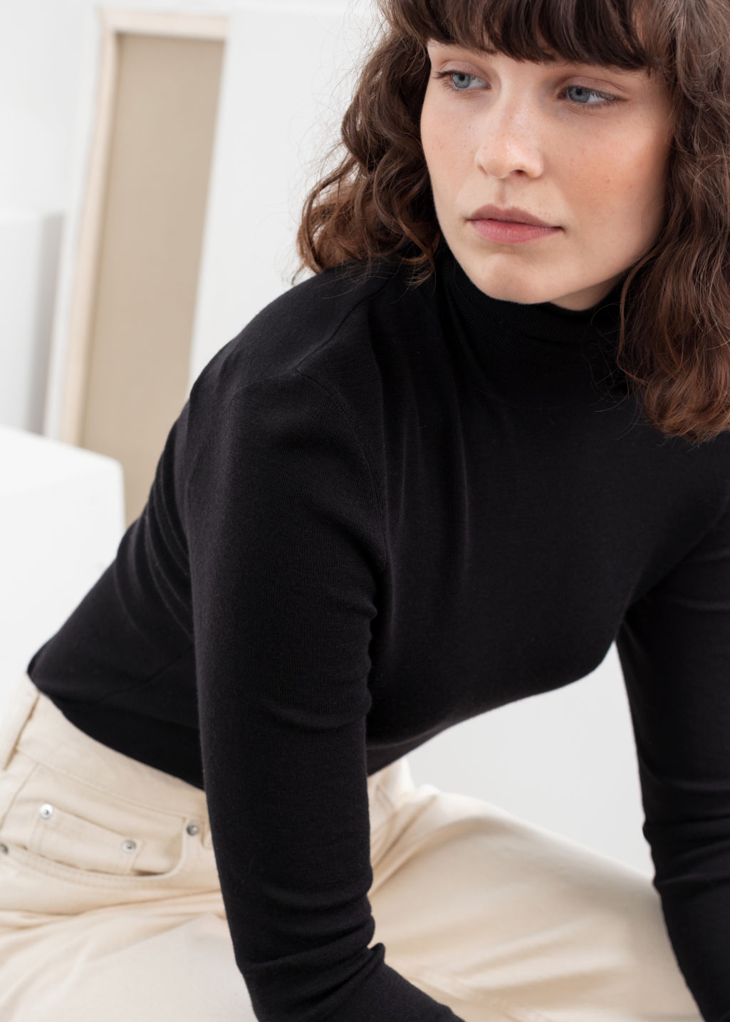 Model back image of Stories merino wool turtleneck in black