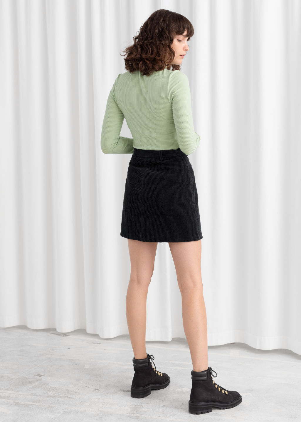 Model back image of Stories fitted stretch rib mock neck top in green