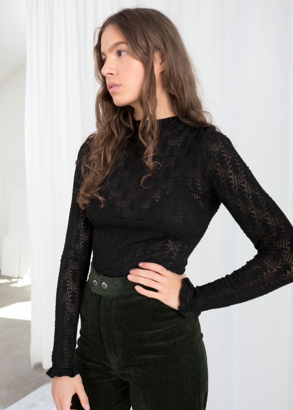 Model front image of Stories eyelet knit top in black
