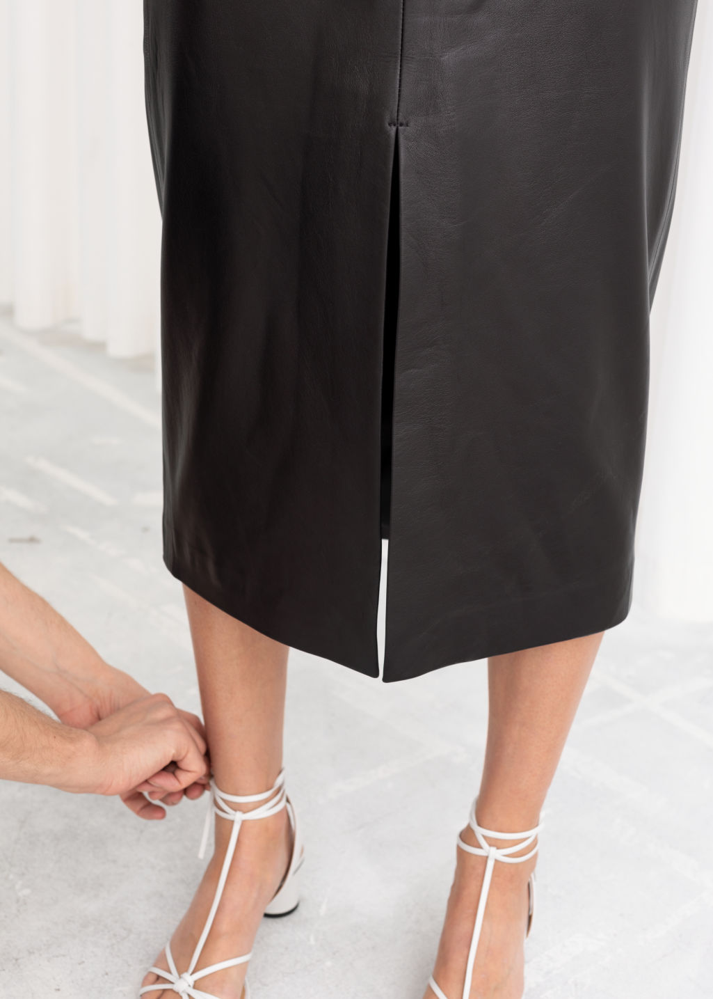 Model back image of Stories front slit leather midi skirt in black