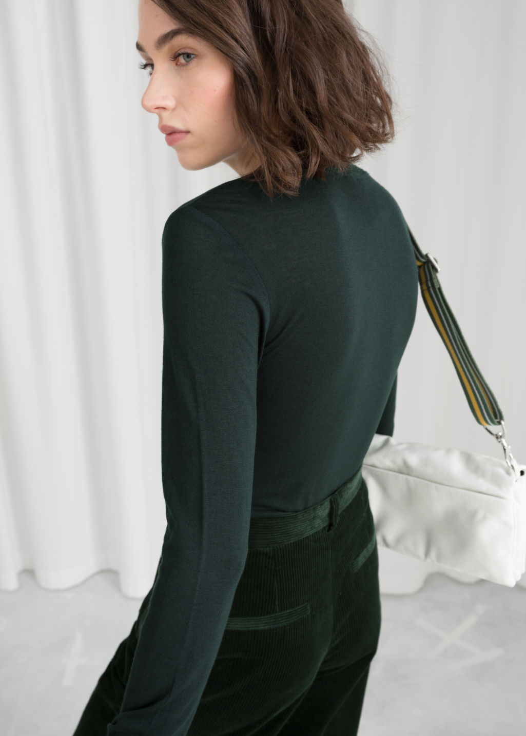 Model back image of Stories semi-sheer fitted top in green