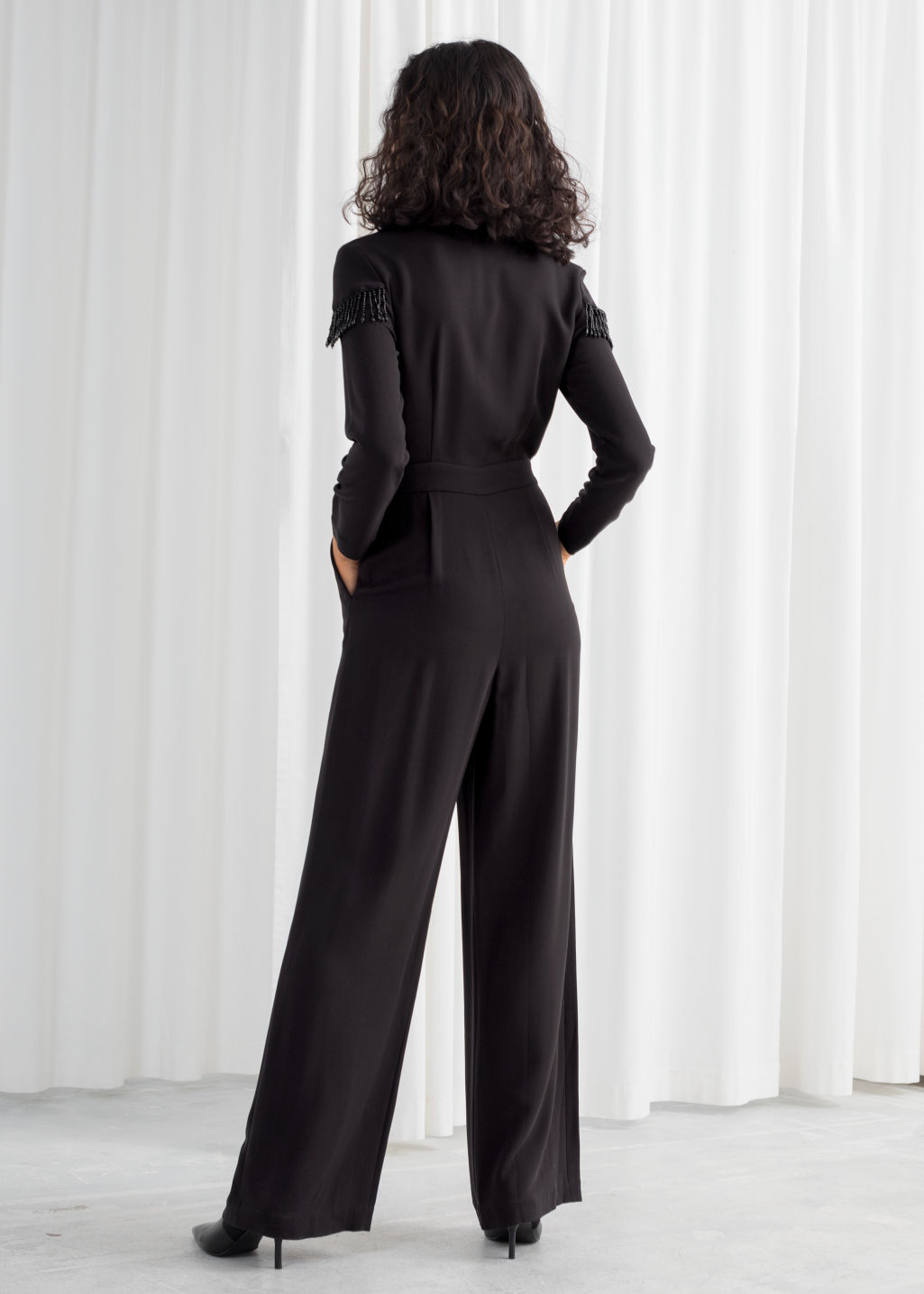 Model back image of Stories beaded long sleeve jumpsuit in black
