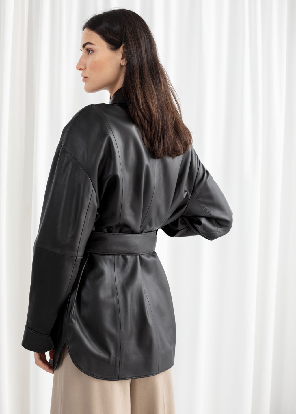 Model back image of Stories oversized belted leather jacket in black