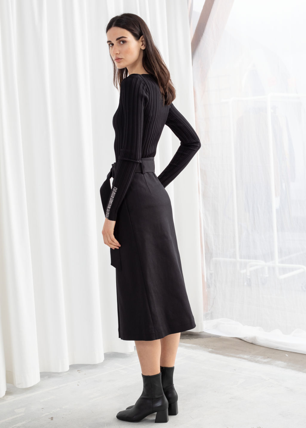 Model back image of Stories belted a-line midi skirt in black